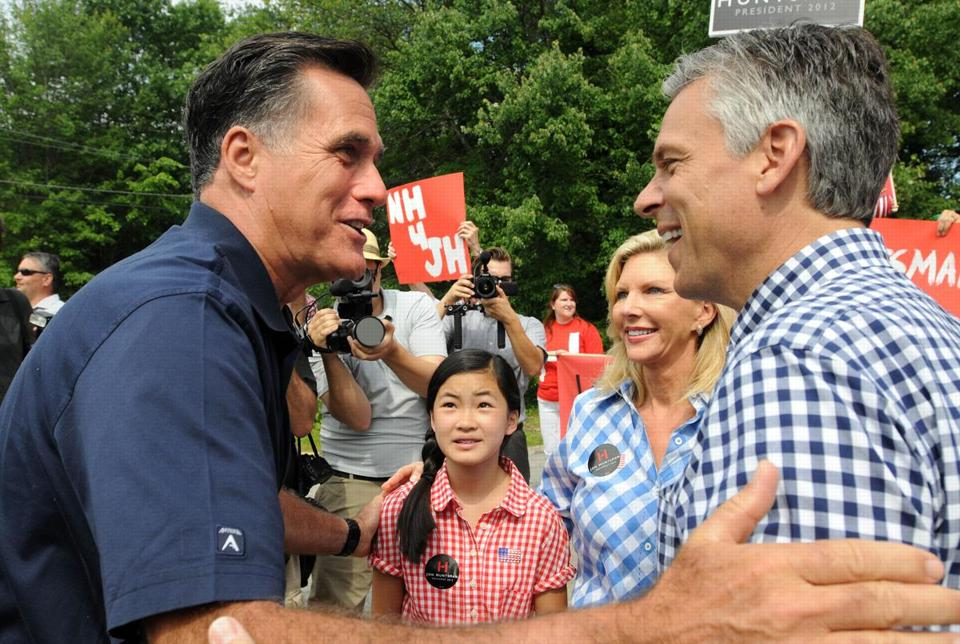 Republican presidential candidates Former Ambassador to China Jon Huntsman (R) and former Massachusetts governor Mitt Romney (L) greet to each other prior to marching in a Fourth of July parade as Huntsman's wife Mary Kaye (2nd R) and daughter Gracie Mei look on July 4, 2011 in Amherst, New Hampshire.