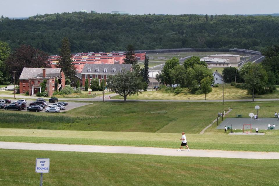 Prisoners walked and played basketball near signs marking the perimeter of the MCI-Shirley prison facility.