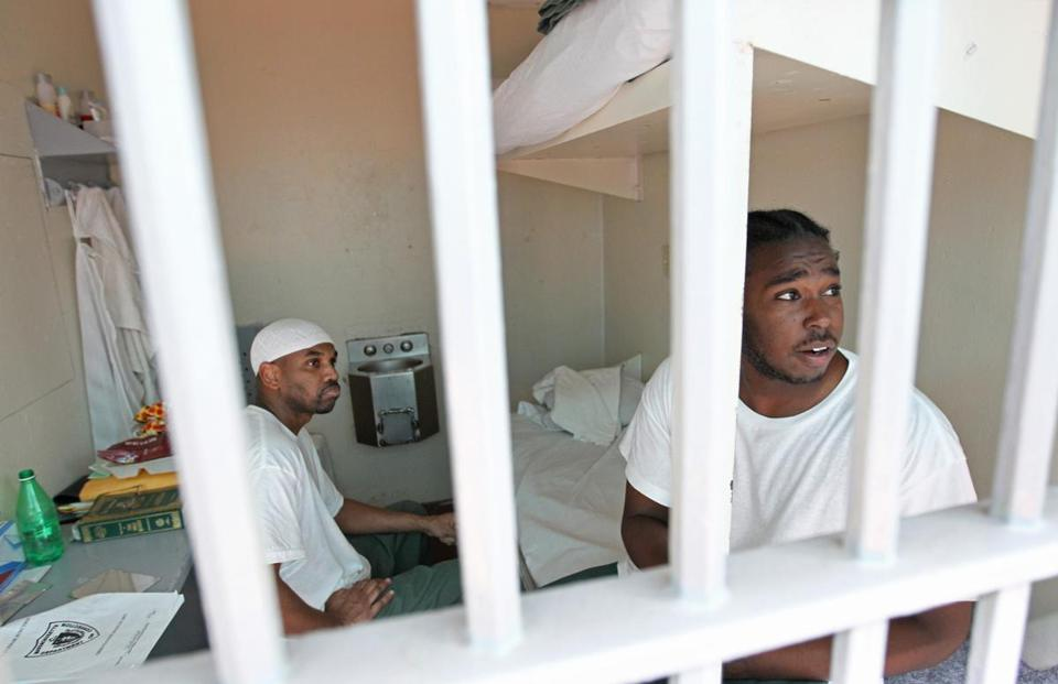Two inmates sit in their prison cell Tuesday at MCI-Cedar Junction in Walpole, where male offenders await a permanent prison assignment.