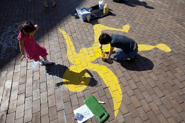 "Alicia Maehara, 3, watched as Shabnam Hosseini , a grad student at Boston University, participated in Sidewalk Sam's chalk on the sidewalk art project during ""Opening Our Doors 2011,"" a free day of art, cultural, and educational events sponsored by 21 institutions in the Fenway."