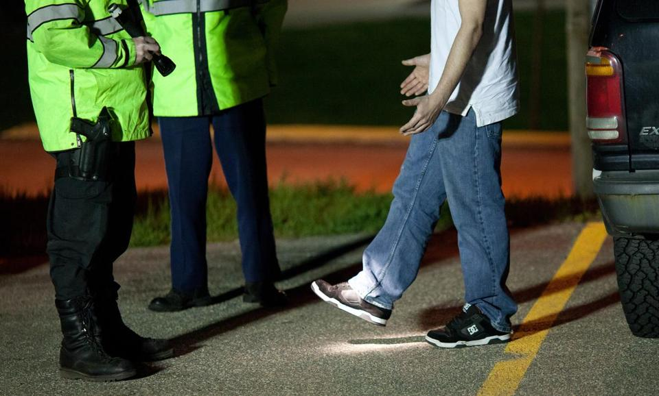 FOR SPOTLIGHT - Massachusetts State Troopers perform a sobriety test on a driver at a sobriety check point operated jointly with the Chicopee Police, on Memorial Avenue in Chicopee on Friday, April 29, 2011. (Matthew Cavanaugh for The Boston Globe)