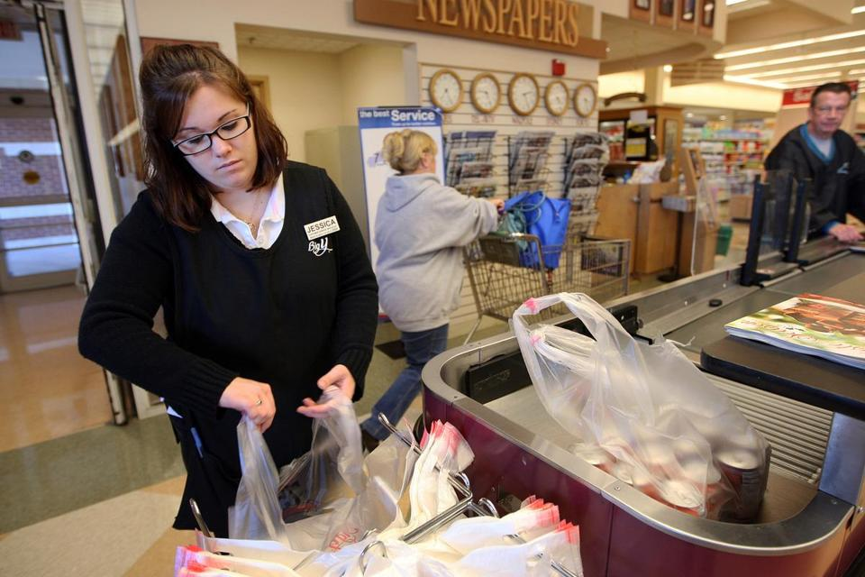 Jessica Campbell bags a customer's groceries on a self-checkout lane at the Big Y supermarket in Walpole.