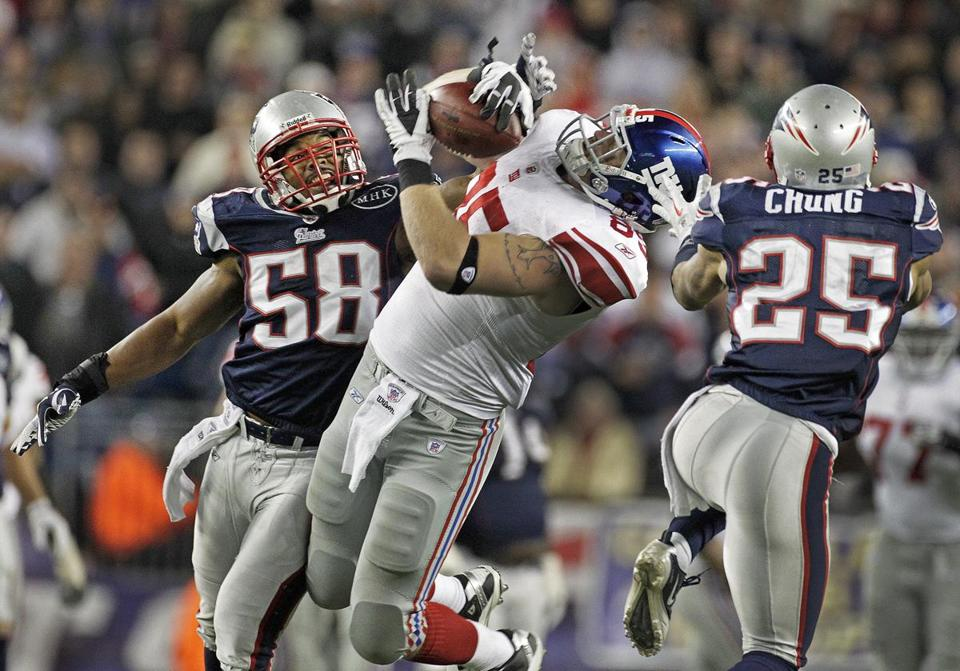 Patriots defenders Tracy White (left) and Patrick Chung can't stop Giants tight end Jake Ballard from hauling in a clutch 28-yard reception late in the game.