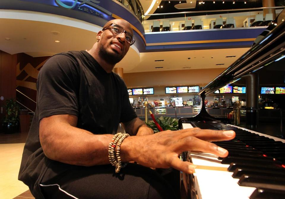At the Showcase Cinema De Lux in Foxborough, Andre Carter takes a break from tackling quarterbacks and instead is tickling the ivories.