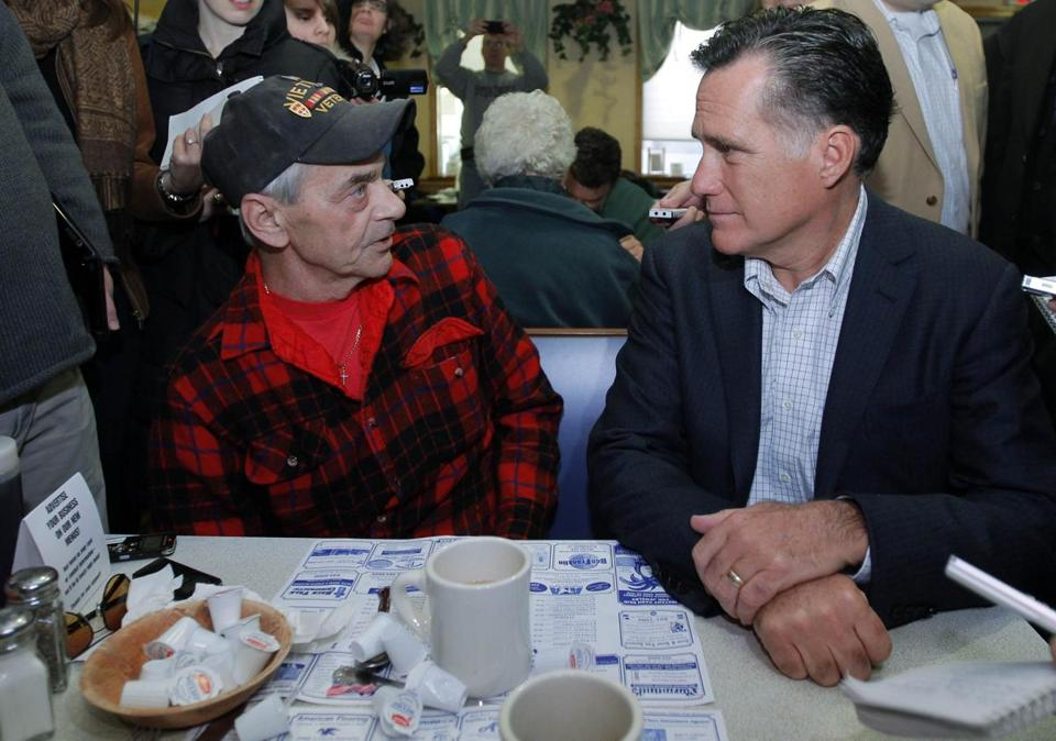 Republican presidential candidate and former Massachusetts Governor Mitt Romney (R) talks to Vietnam War veteran Bob Garon at Chez Vachon Restaurant in Manchester, New Hampshire December 12, 2011. Garon, who says he is gay, asked Romney about the Defense of Marriage Act. REUTERS/Brian Snyder (UNITED STATES - Tags: POLITICS)