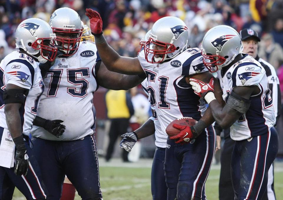 Patriots linebacker Jerod Mayo (51) celebrated with teammates after he made an interception in the fourth to help seal the win against the Redskins.