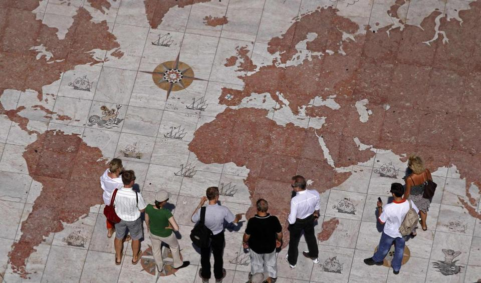 People walk over a world map engraved in marble in Lisbon September 14, 2011