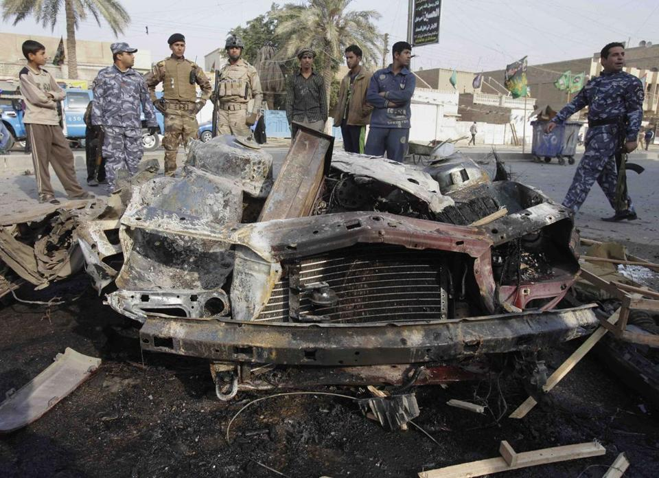 Iraqi security forces gathered at the scene of a car bomb attack in Baghdad today.