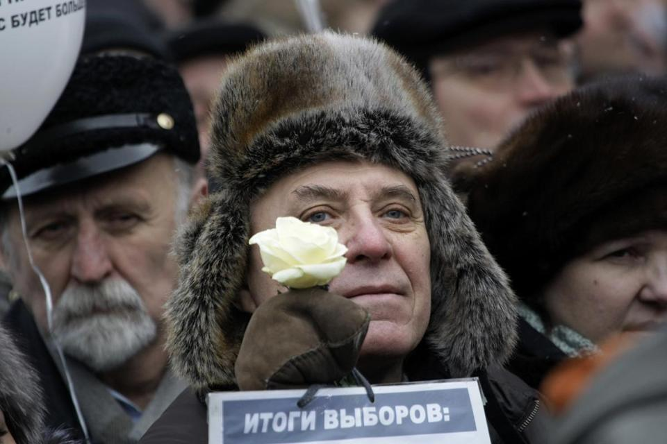 "A protester held a white flower and a paper with the words ""election results"" during a rally today in Moscow."