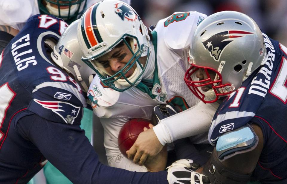It's a big catch for Patriots defensive linemen Shaun Ellis (left) and Brandon Deaderick in the third quarter as they team up to sack Dolphins quarterback Matt Moore for a 10-yard loss.