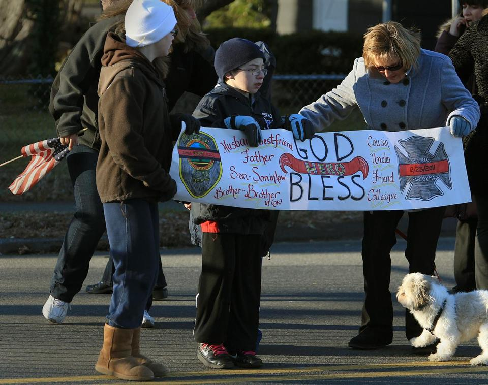 Peabody, MA 122911 Madison Conrad (Cq), 12 (left), Tyler Conrad (cq), 13, and Lisa Roberts (cq), all from Peabody hold a sign during the wake of fallen Peabody firefighter James M. Rice at the Conway Cahill- Brodeur Funeral Home in Peabody on December 29, 2011. (Essdras M Suarez/ Globe Staff)/ MET