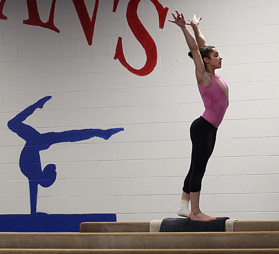 Alexandra Raisman, a 17-year-old senior at Needham High, is on the beam as she points toward the London Olympics.