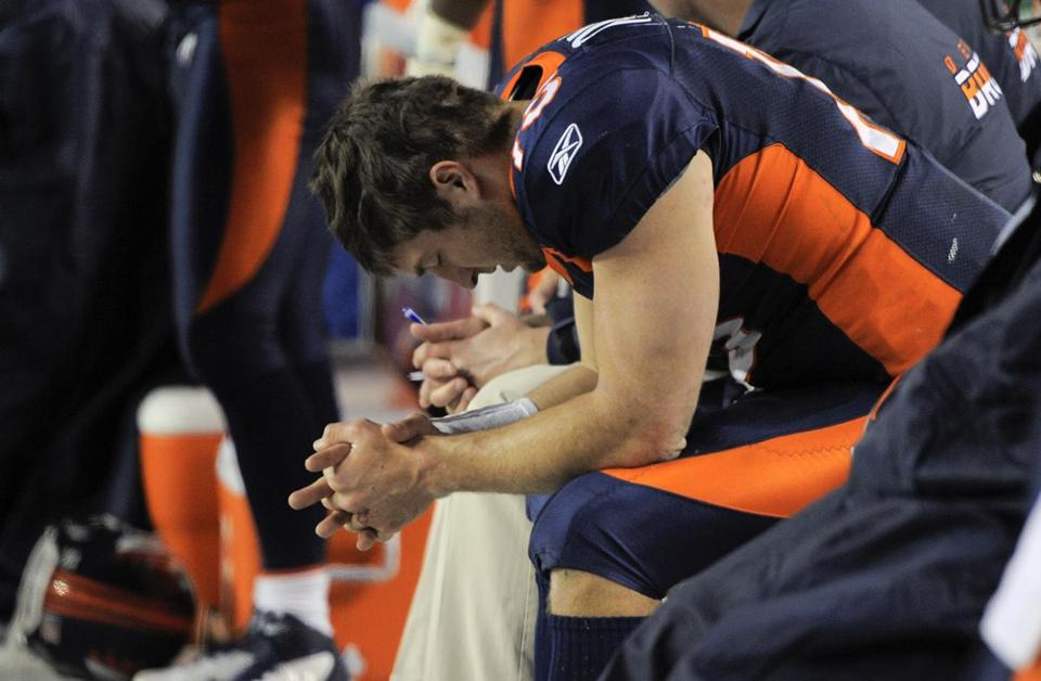 Denver Broncos quarterback Tim Tebow (15) prays while sitting on the bench late in the fourth quarter of an NFL football game against the Kansas City Chiefs, Sunday, Jan. 1, 2012, in Denver. (AP Photo/Jack Dempsey)