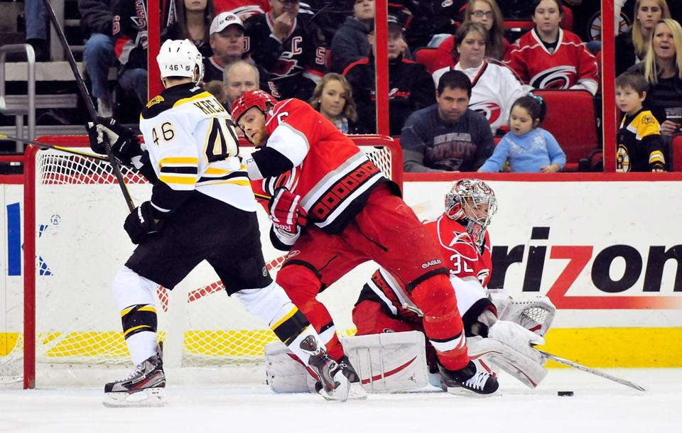 RALEIGH, NC - JANUARY 14: Cam Ward #30 of the Carolina Hurricanes watches the puck as teammate Tim Gleason #6 drives David Krejci #46 of the Boston Bruins away from the net during play at the RBC Center on January 14, 2012 in Raleigh, North Carolina. (Photo by Grant Halverson/Getty Images)