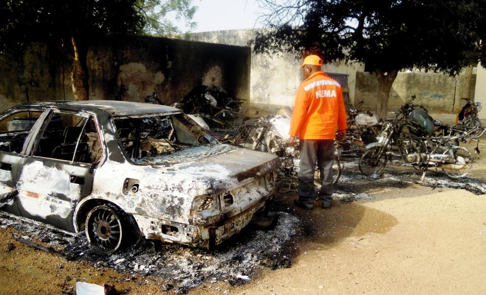 A rescue worker inspected the burnt-out wreckage of cars and motorcycles destroyed by multiple explosions in the Marhaba area of the northern Nigerian city of Kano today.