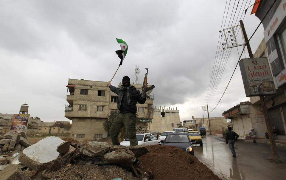 This image reportedly shows a Syrian soldier who defected and joined the Free Syrian Army, as he waved a Syrian independence flag in the Damascus suburb of Saqba today.