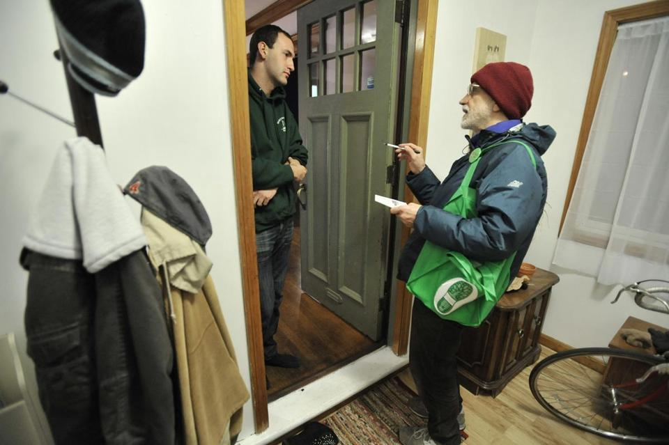 Ed Loechler, right, speaks with Tom Fuchs, 22, a tenant about Utility company's renewable energy programs during a walk through his neighborhood in Brookline with literature explaining renewable energy programs. Despite publicity, utility companies have seen little participation in their renewable energy programs. JOSH REYNOLDS FOR THE BOSTON GLOBE (Science, Able)