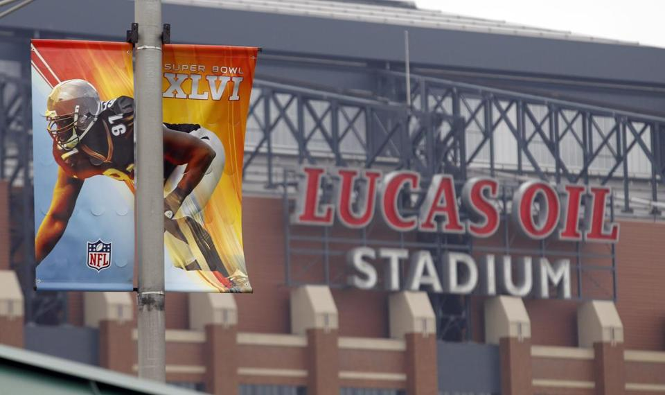 Banners hang on light poles near Lucas Oil Stadium as preparations continue for Super Bowl XLVI in Indianapolis, Monday, Jan. 23, 2012. The New England Patriots will face the New York Giants on Feb. 5. (AP Photo/Michael Conroy)