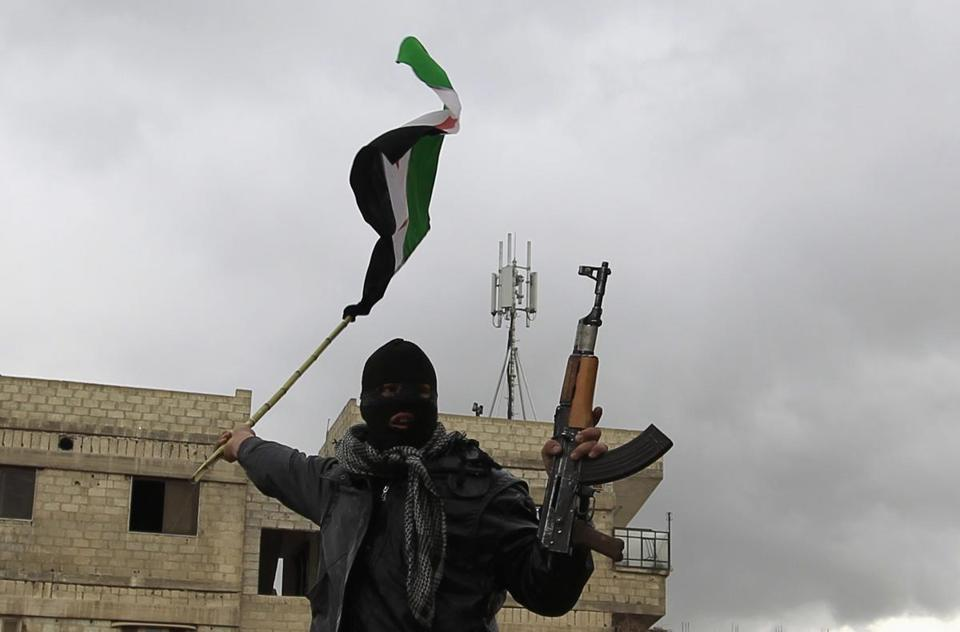 A Syrian soldier, who has defected to join the Free Syrian Army, holds up his rifle and waves a Syrian independence flag in Saqba, in Damascus suburbs, January 27, 2012. REUTERS/Ahmed Jadallah (SYRIA - Tags: CIVIL UNREST POLITICS MILITARY)