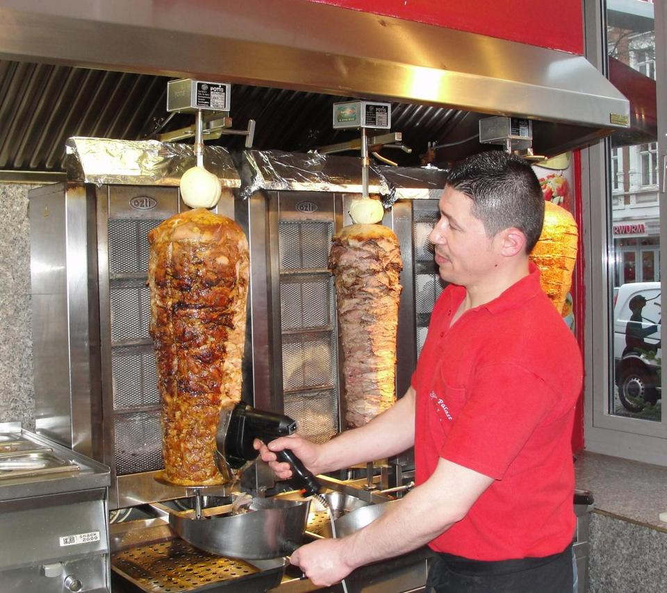 At Sultan Palast in Luebeck, Harun Tetik shaves meat for a doner kebab sandwich, a dish served throughout Germany.