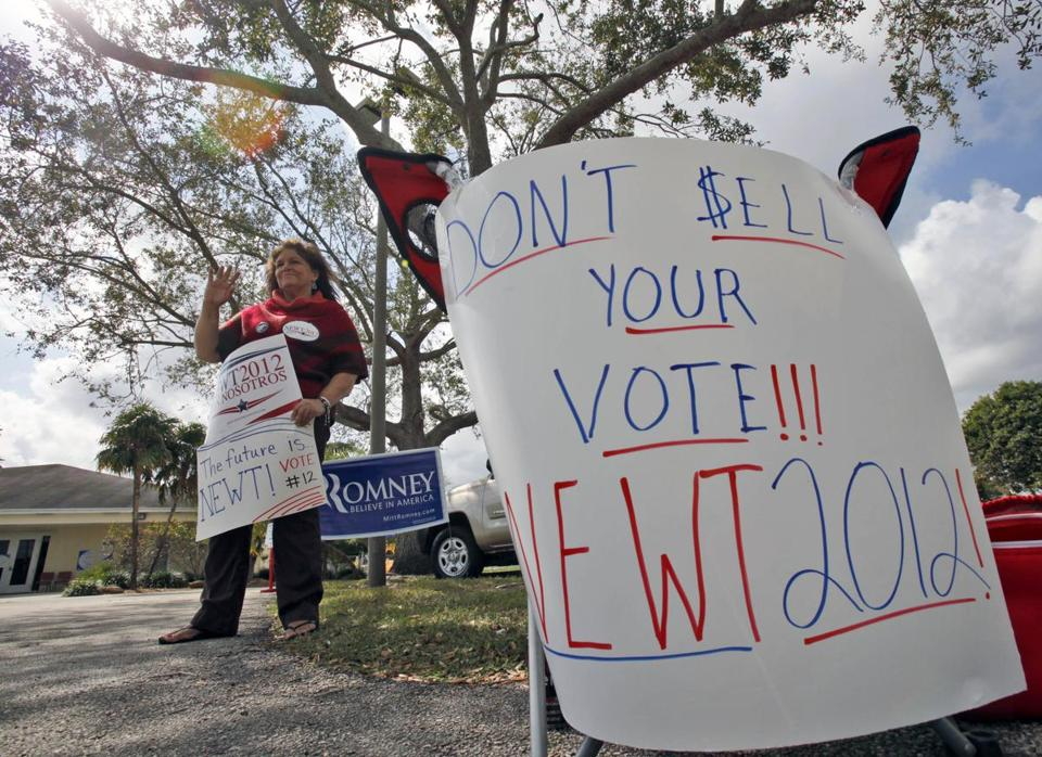Newt Gingrich supporter Luz Gonzalez of Miami waved to a passing car as she stood outside a polling station today.