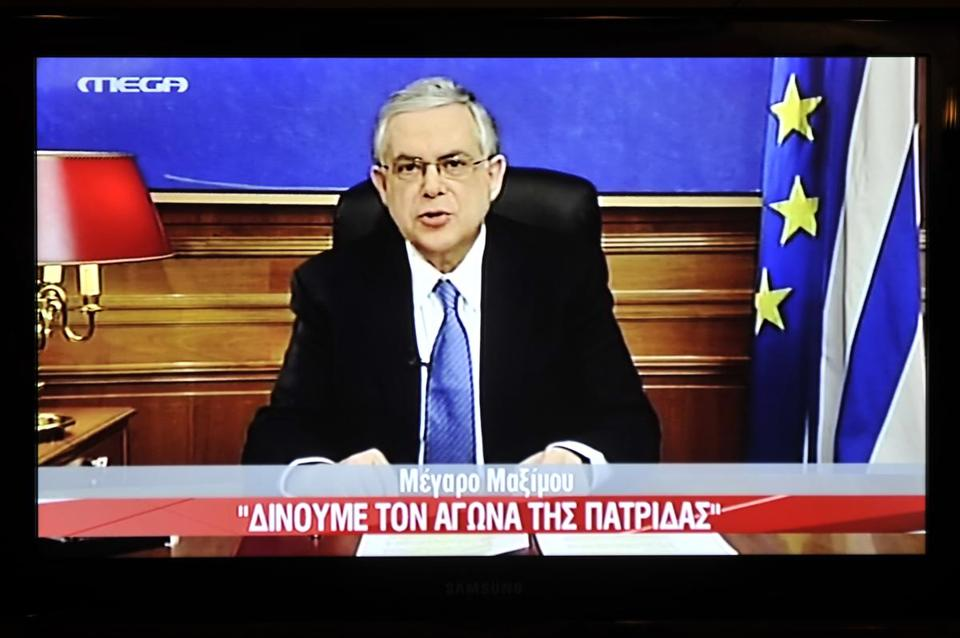 A picture of a TV screen shows Greek Prime Minister Lucas Papademos during his televised address to the nation.