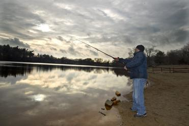 A man fished in Houghton's Pond in Milton today, as a winter storm left much less precipitation than was forecast.