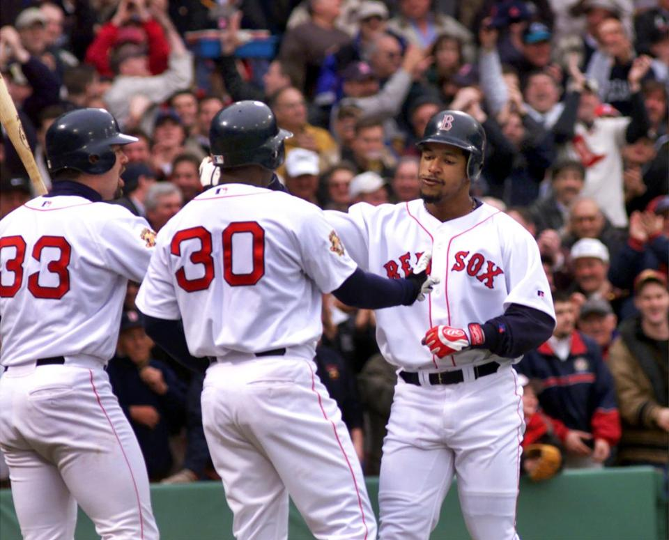 Manny Ramirez drew kudos from Jason Varitek, left, and Jose Offerman after blasting a three-run home run on the first pitch he saw at Fenway Park as a member of the Red Sox.