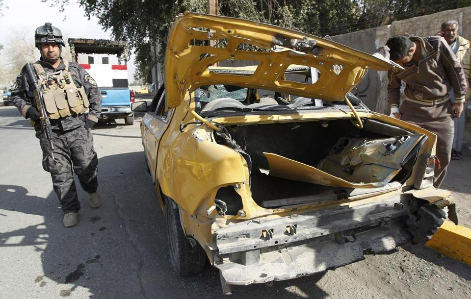A police officer inspected a damaged vehicle after a bomb attack in Baghdad's Karrada district today.