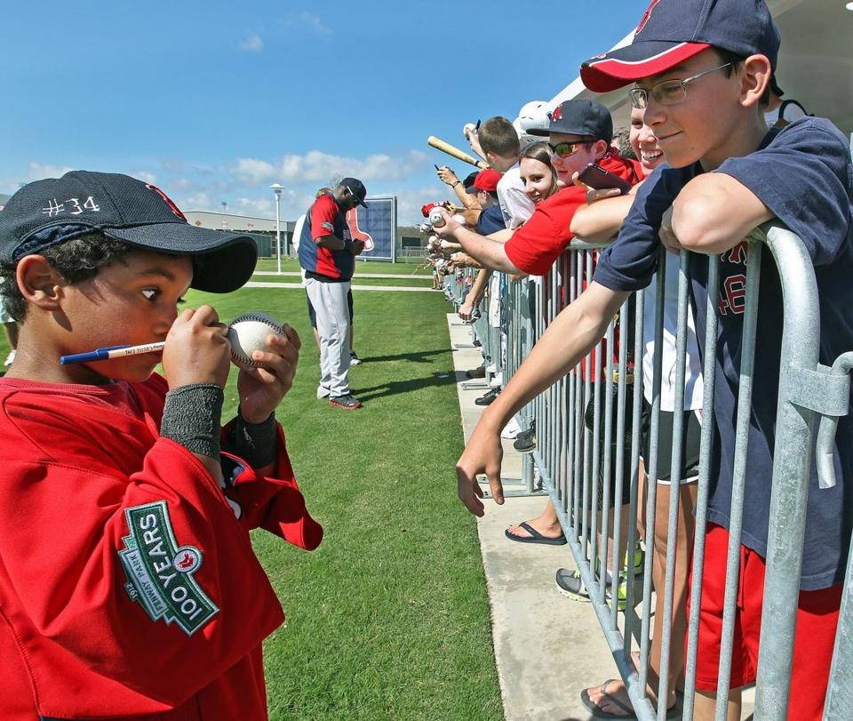 As Red Sox DH David Ortiz (backround, center) signed autographs for a large group of fans in Fort Myers, Fla., on Thursday, one fan asked his son D'Angelo, who had been sitting on the grass waiting for his dad, if he would sign a ball for him, and the youngster obliged.