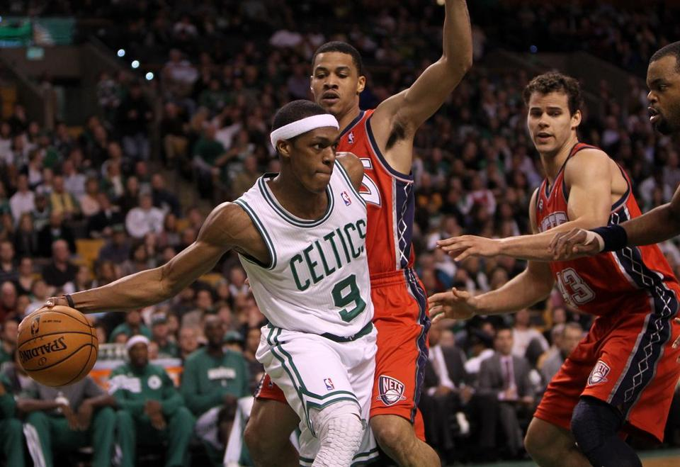 Appearing unfazed, Celtics point guard Rajon Rondo (9) calmly dishes off when a trio of Nets converge on him.