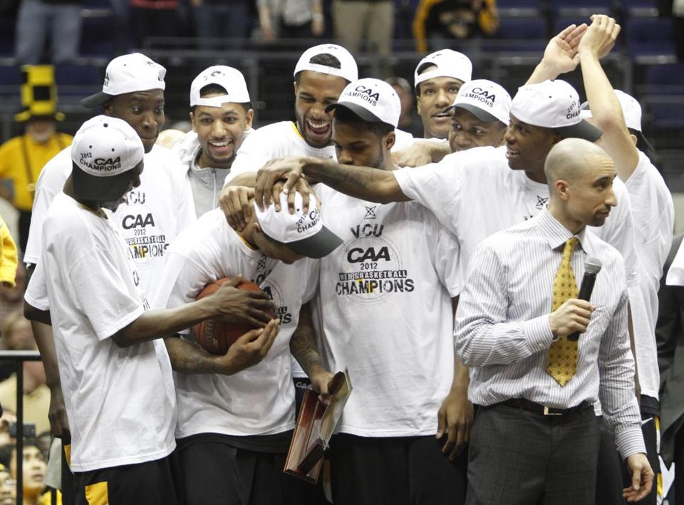 VCU players congratulated MVP Darius Theus, center, after winning the Colonial Athletic Association Championship.