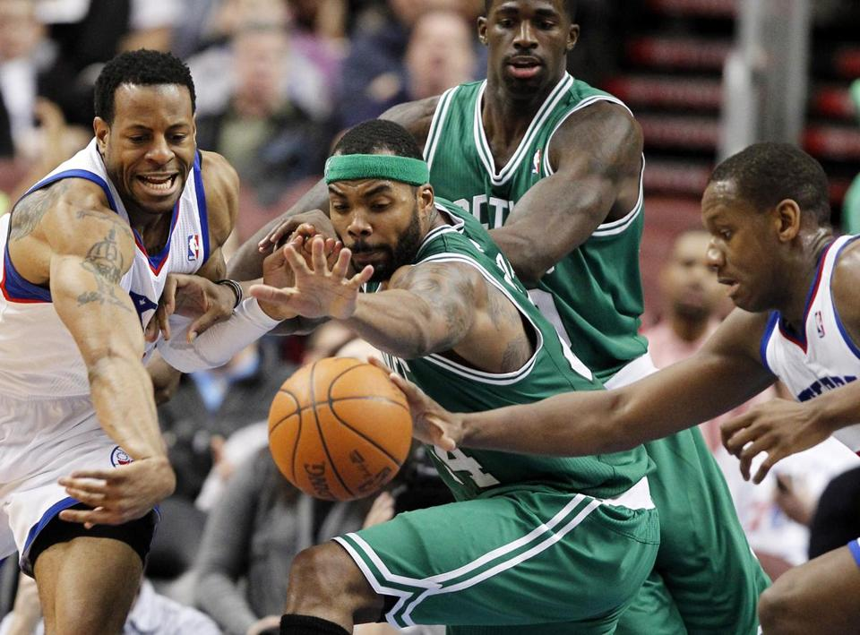 Philadelphia 76ers forward Andre Iguodala, left, and center Spencer Hawes, right, battled for the ball with Celtics forward Chris Wilcox, center foreground, with Brandon Bass in the first of Philadelphia's blowout win Wednesday.