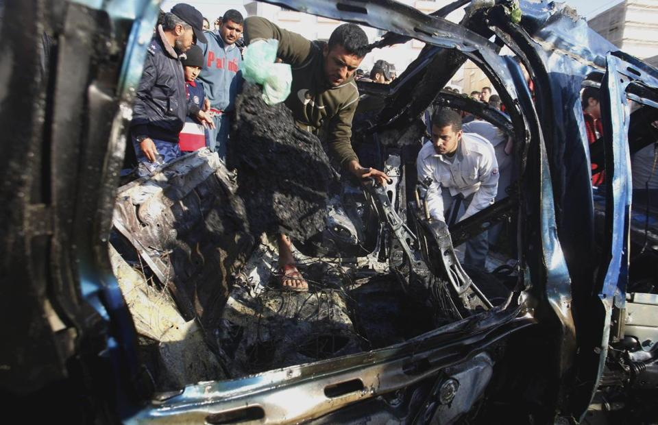 Palestinians gathered around the wreckage of a car targeted in an airstrike in Gaza City on Friday.