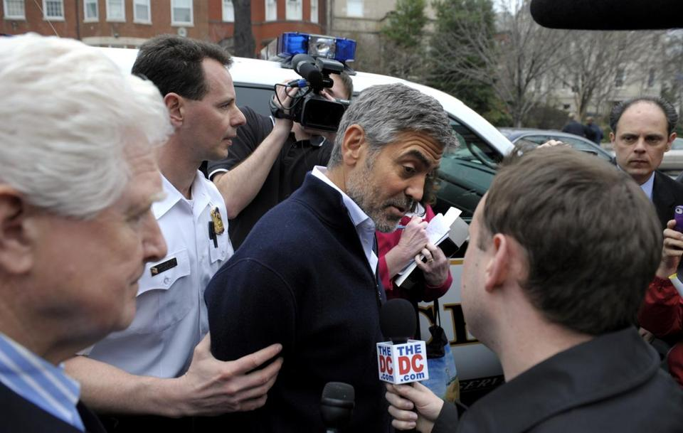 Actor George Clooney was led to a police vehicle after being arrested during a protest at the Sudan Embassy in Washington.