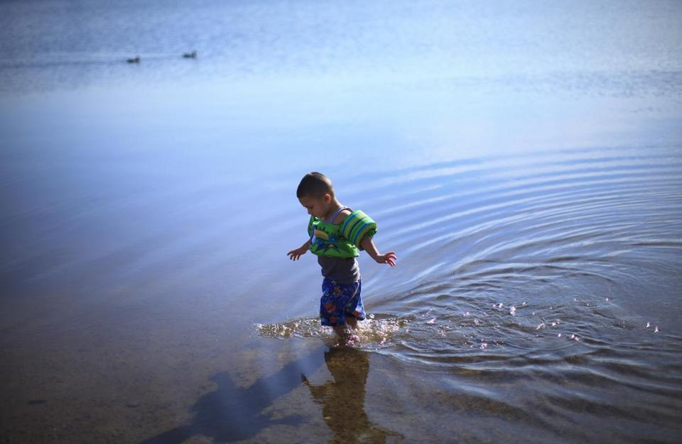 Three-year-old Dennis Flores went for a dip in the water at Memorial Beach in the Mystic River Reservation in Winchester on Monday, the last official day of winter.
