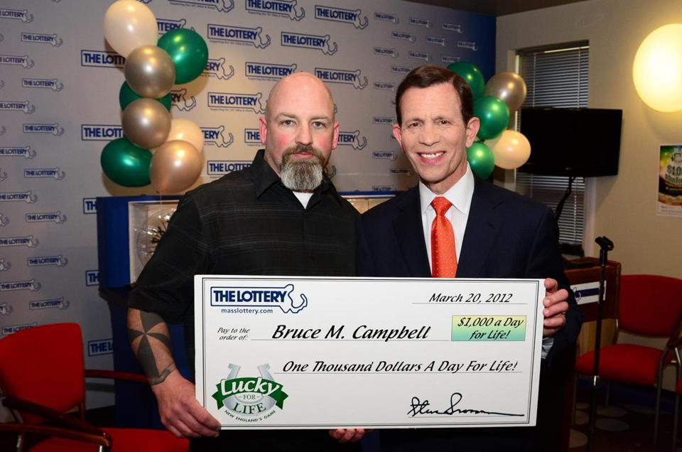 State Treasurer Steve Grossman (right) presented Bruce Campbell, Lucky for Life's first top prize winner, with a ceremonial check for $1,000 a day for life.