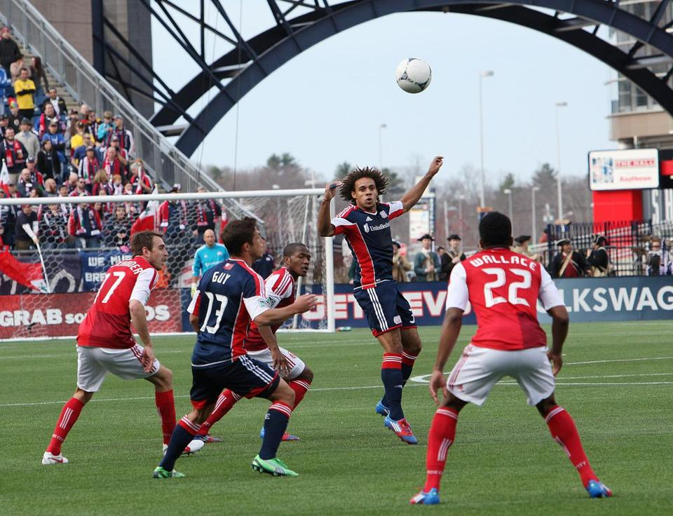 Kevin Alston tries to clear traffic in front of the Timbers' net with a header during the Revolution's home opener.