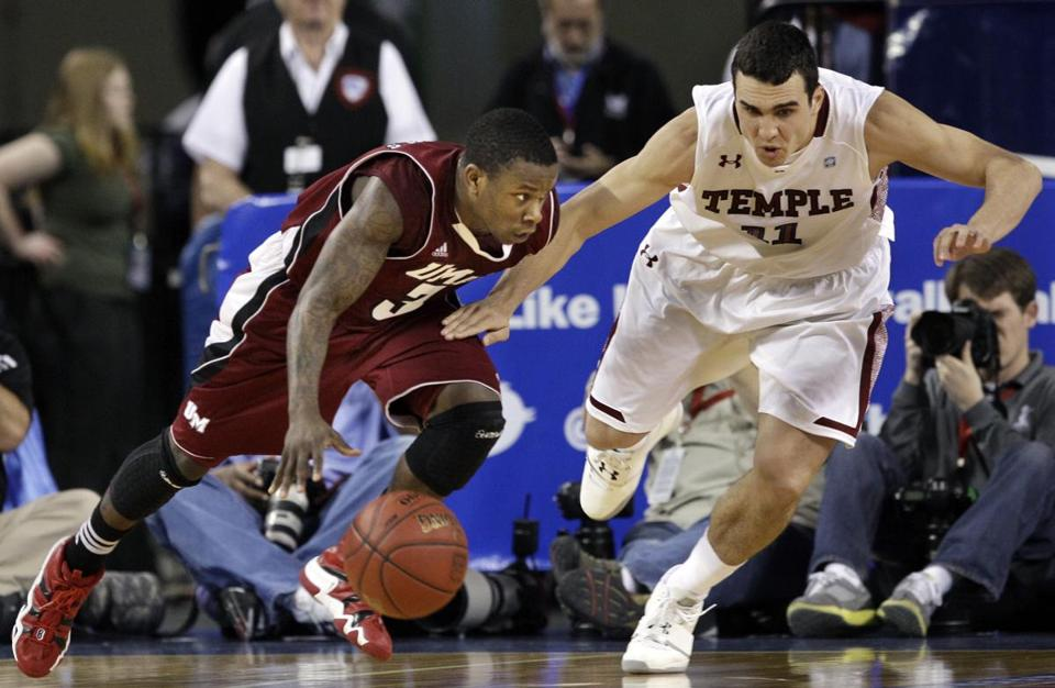 Massachusetts' Chaz Williams dribbled the ball as Temple's T.J. DiLeo tried to make a steal during the second half of an NCAA college basketball game in the quarterfinals of the Atlantic 10 men's tournament.