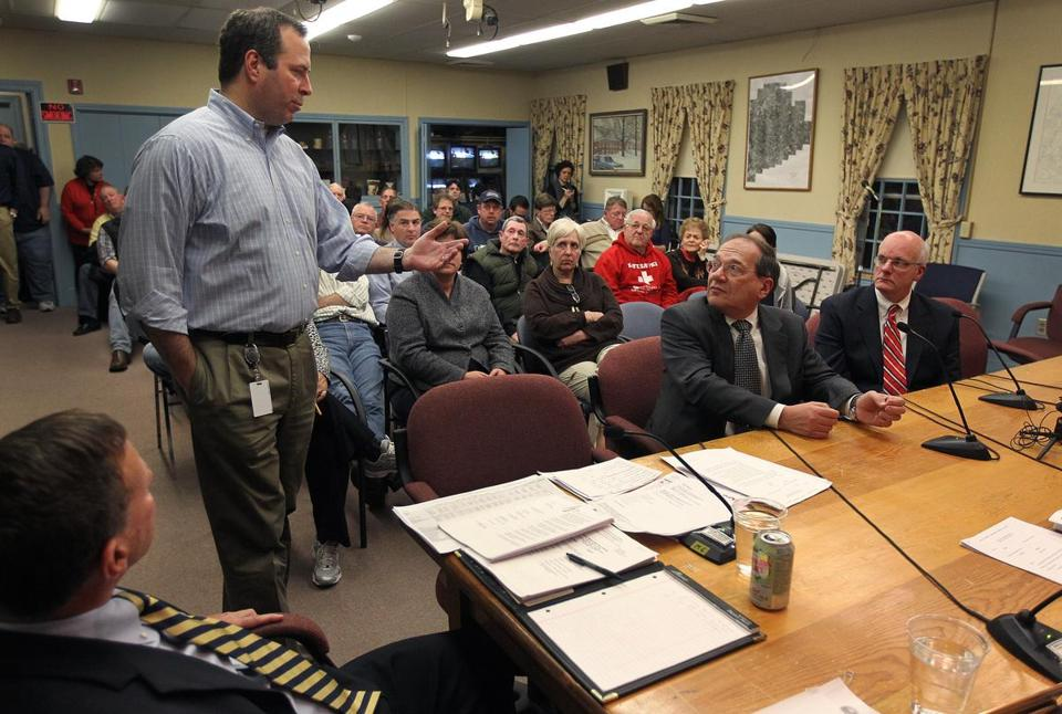 James Cobery, (standing, left), a vice president at The Kraft Group, addressed Foxborough town officials Tuesday night.