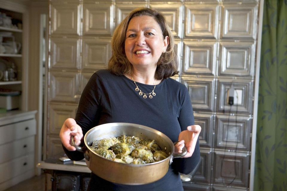 Brigitte Scheinmann poses for a portrait with a pot of her Tunisian sytle Yabrak dish in her kitchen in West Roxbury, MA.