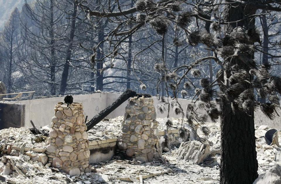 The remains of a home sat among burned trees in Conifer, Colo., on Wednesday after a fire believed to have been started by a controlled burn. The fire killed two people and destroyed dozens of homes, and was not yet contained.