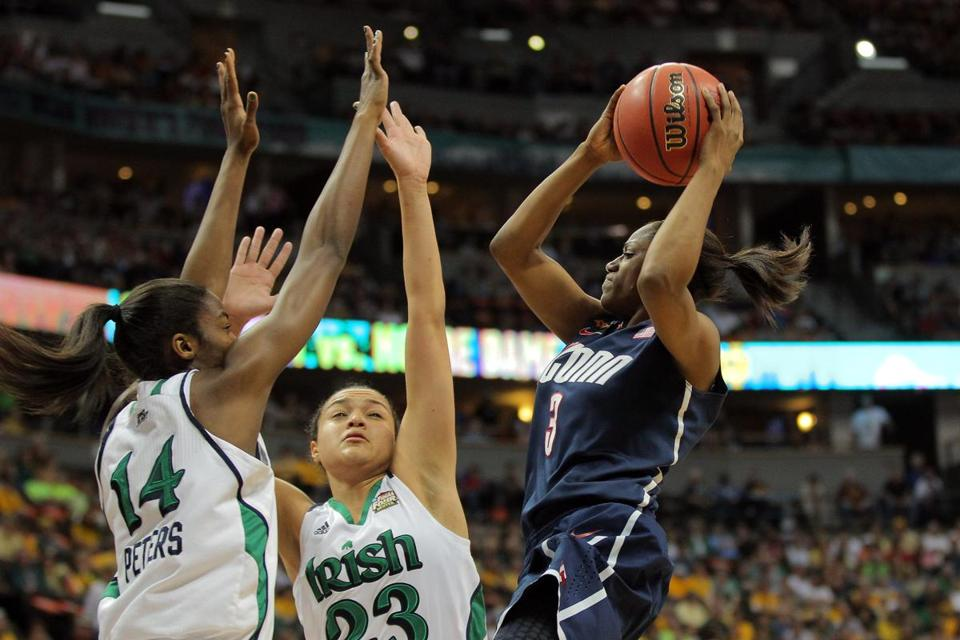 UConn's Tiffany Hayes (right) has her path to the hoop blocked by Notre Dame's Devereaux Peters (left) and Kayla McBride.