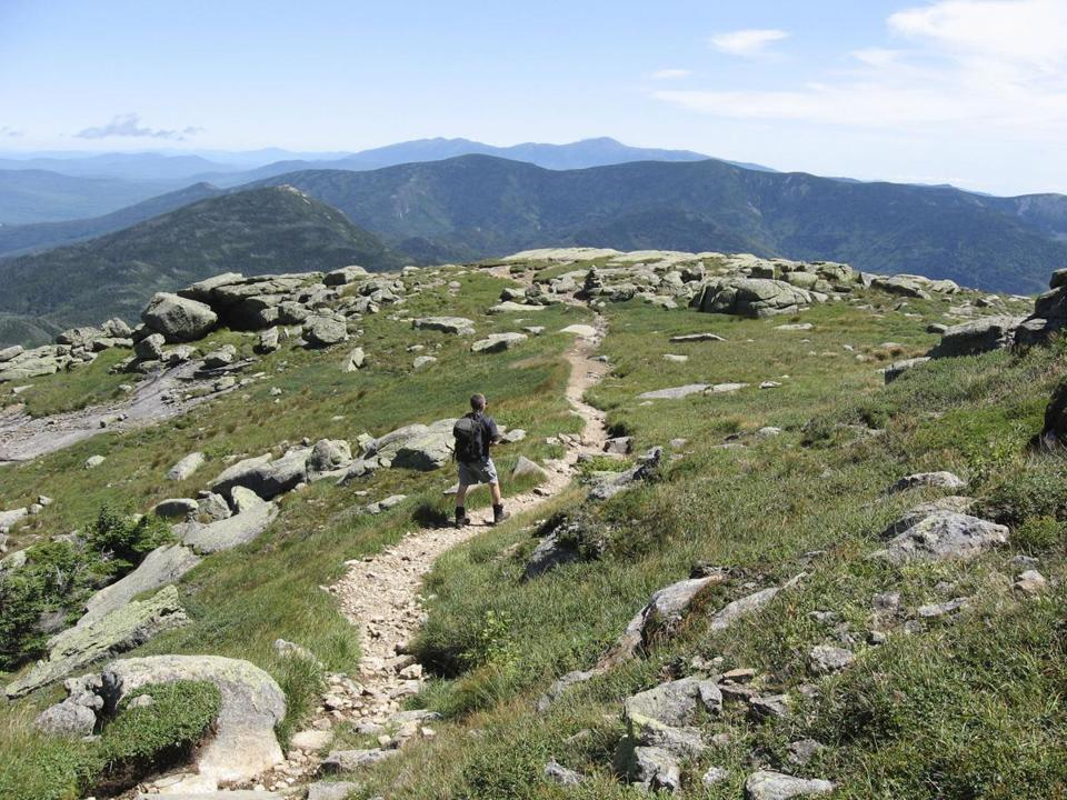 A hiker explores the summit of Mount Lafayette, the highest point on Franconia Ridge, in the Granite State.