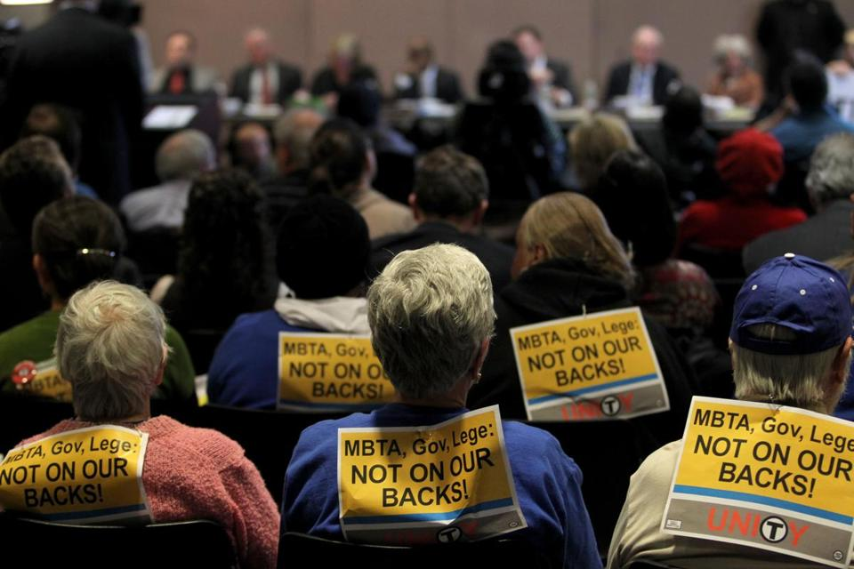 Opponents of the proposed MBTA fare increases wore signs at a board meeting at the State Transportation Building.