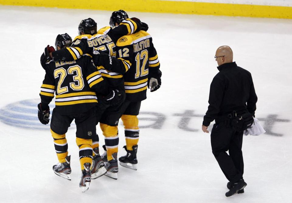 Johnny Boychuk (center) was helped off the ice by teammates Chris Kelly (left) and Brian Rolston (right) during the third period of Tuesday's game against the Pittsburgh Penguins.