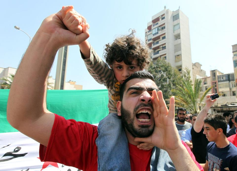 An anti-government protester carried his son at a demonstration against President Bashar Assad on Friday.