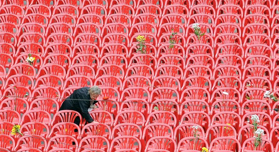 A woman left flowers on some of the 11,451 empty red chairs that were assembled on the main street of Sarajevo on Friday to honor those who were killed during the siege of the city. The city was marking the 20th anniversary of the start of the Bosnian war.