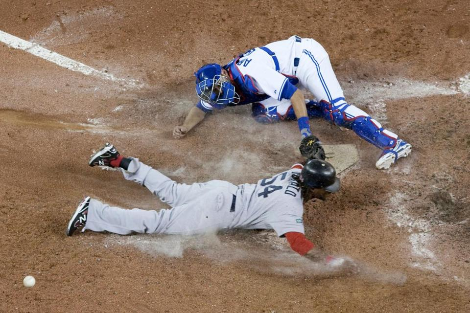 Blue Jays catcher J.P. Arencibia can't hold on to the ball or prevent the Red Sox' Darnell McDonald from sliding home safely in the ninth inning.