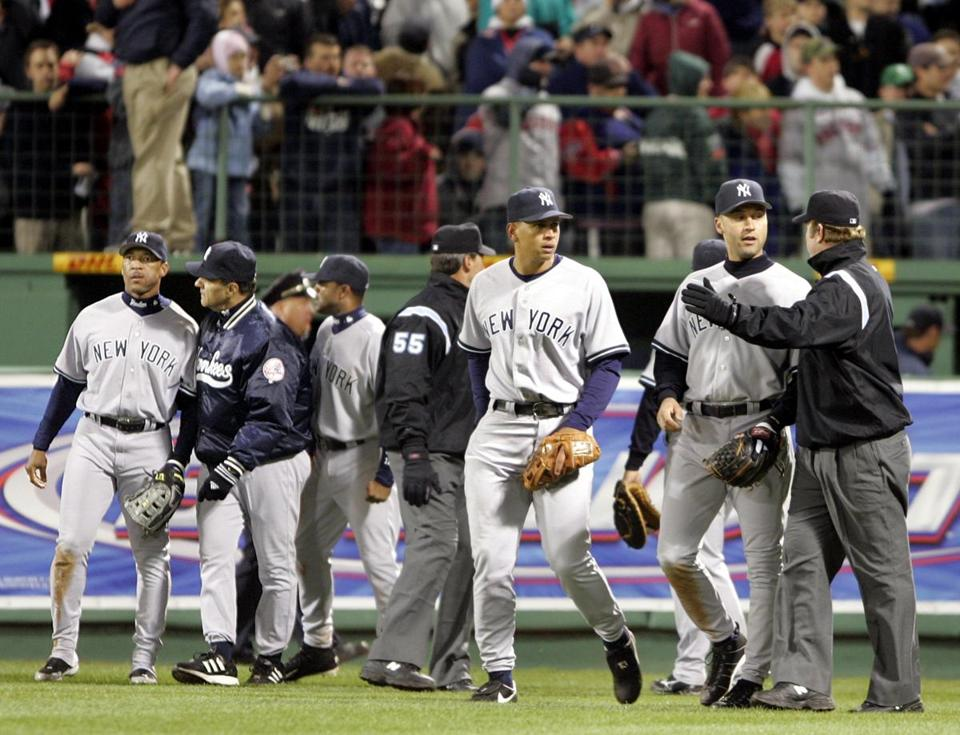 Yankees manager Joe Torre led Gary Sheffield, left, away following an incident with a fan in the bottom of the eighth inning.